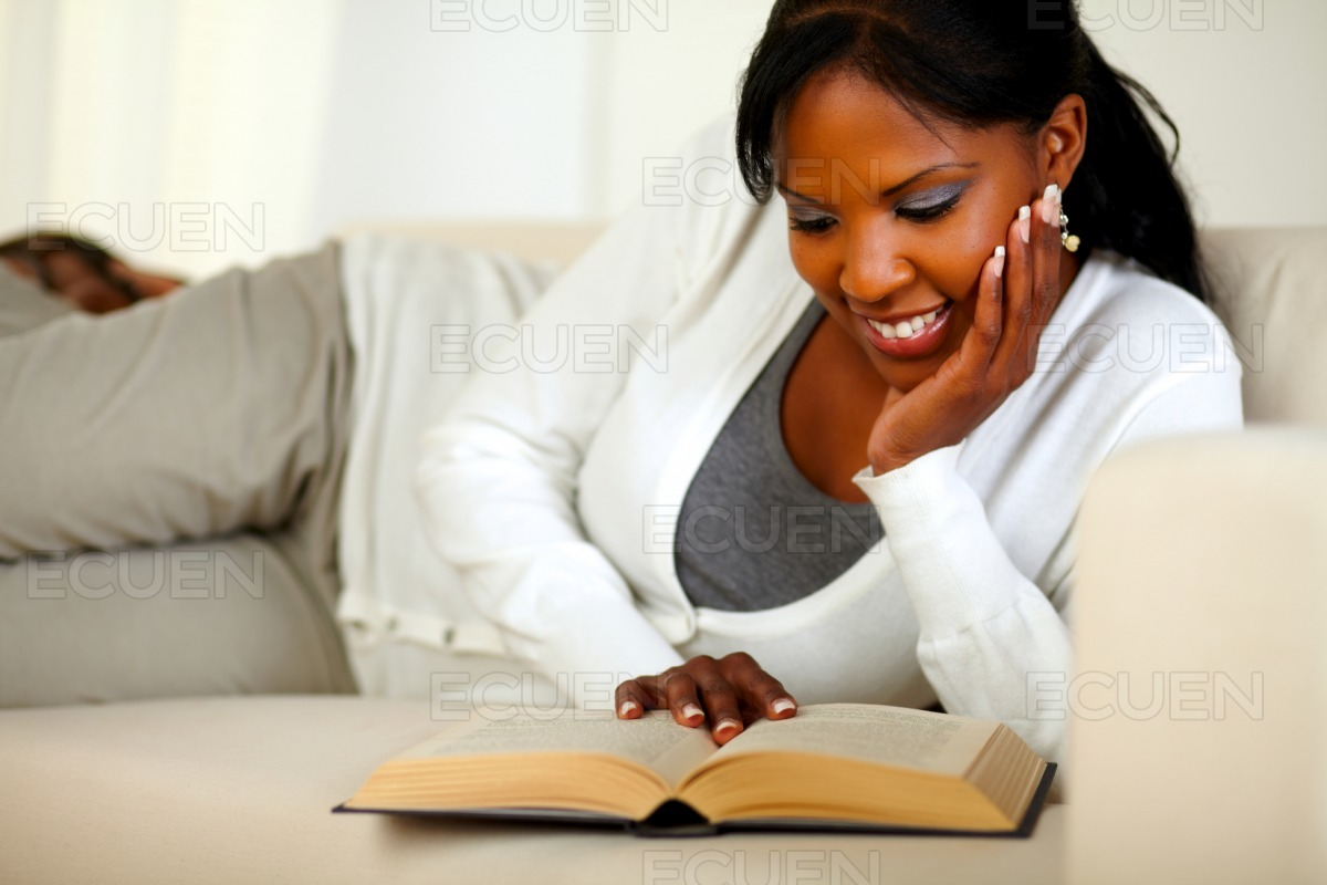 Young relaxed woman reading a book at home stock photo