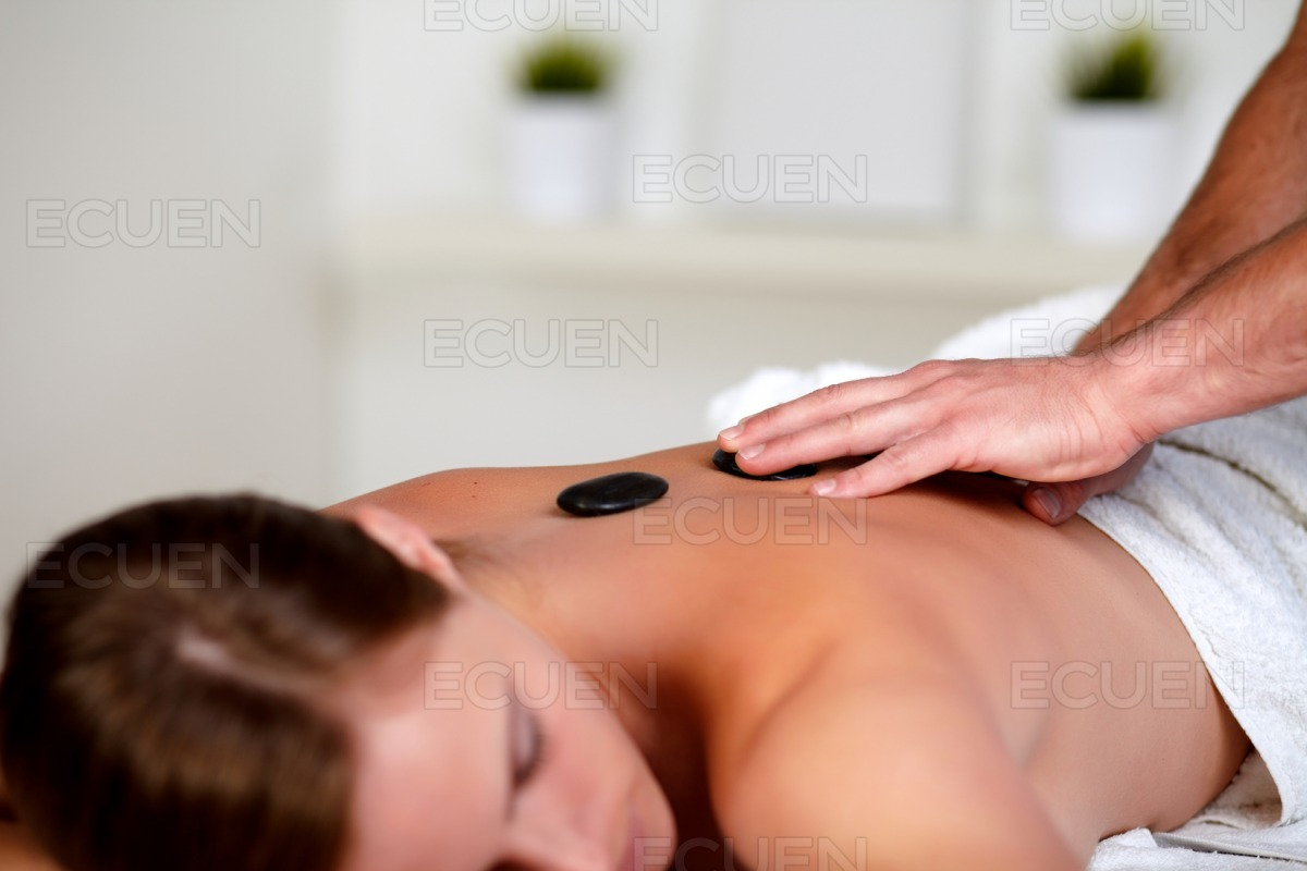 Young woman getting a massage with hot stones stock photo