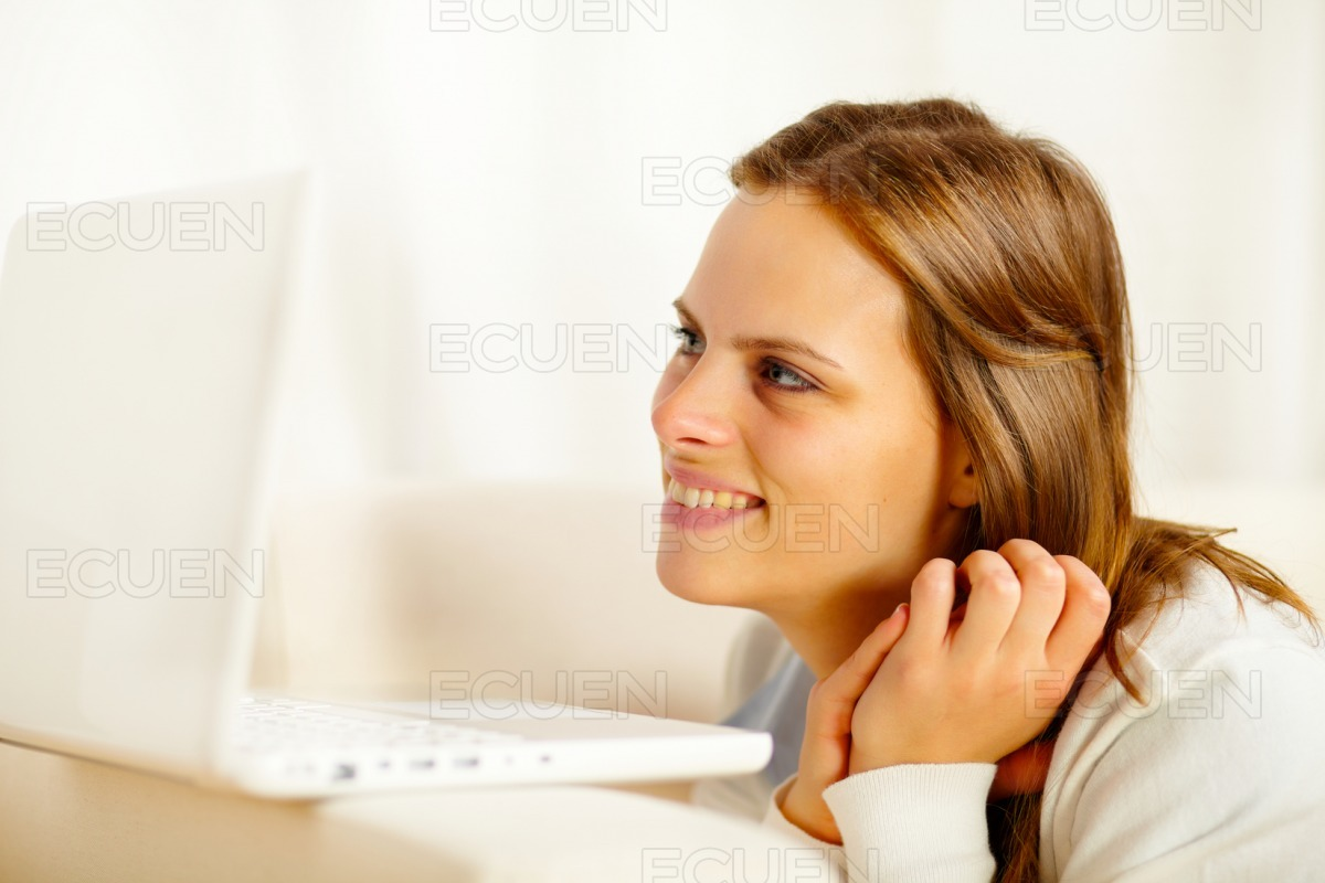 Young woman lying on sofa with a laptop stock photo