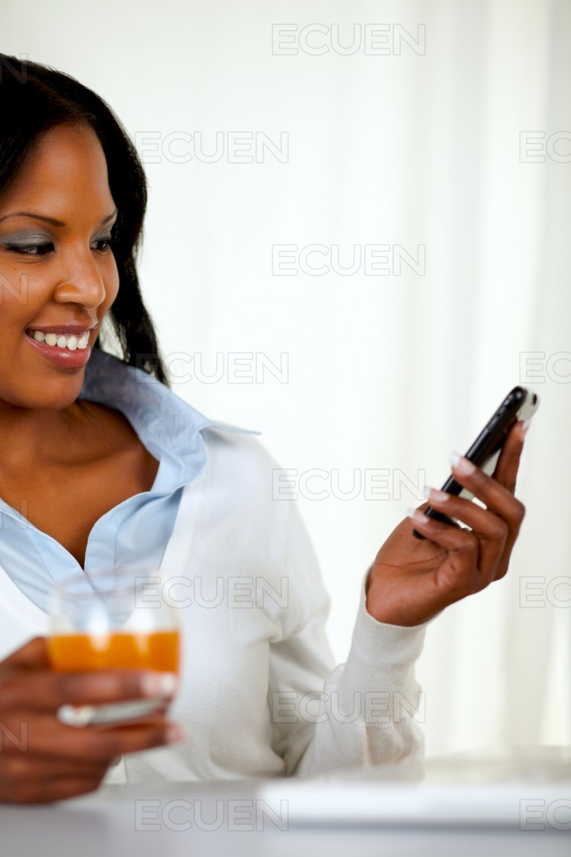 Young woman sending a message by cellphone stock photo