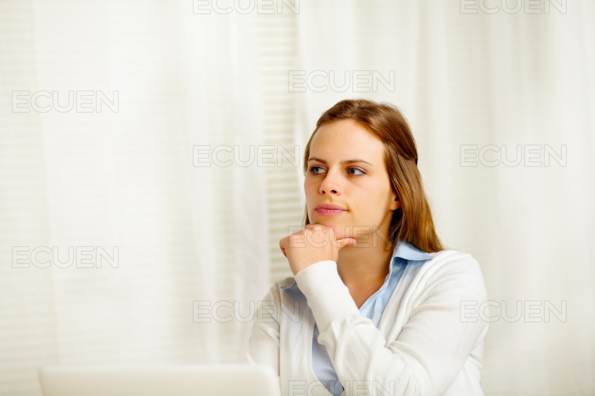 Young woman thinking in from laptop stock photo