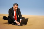 A business man relaxing and sit down on the sand of the desert a