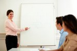 Adult female teacher pointing at whiteboard