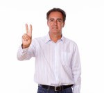 Adult hispanic man with victory sign