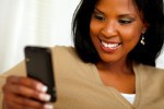 Afro-american girl browsing the Internet on phone