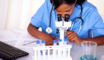 Afro-american nurse woman using a microscope