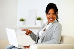Afro-american woman pointing to laptop screen