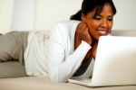 Afro-american young woman reading on laptop screen