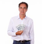 Attractive male standing and holding dollars