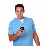 Attractive nurse man texting with his cellphone