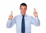 Attractive young businessman crossing his fingers