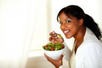 Beautiful girl eating vegetable salad