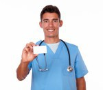 Charming male nurse holding a blank business card