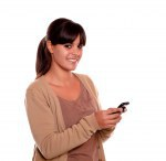Charming young woman sending message by cellphone