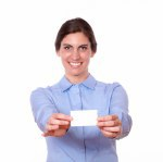 Charming young woman smiling holding a blank card
