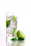 Composition of one mojito, one lime and a mint leaf on isolated background.