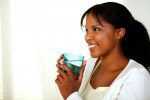 Cute young woman smiling and drinking fresh water