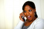 Excited young woman screaming and talking on phone