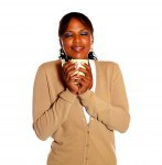 Friendly young woman drinking a mug of coffee