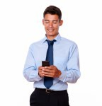Handsome businessman texting on his cellphone