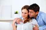 Happy young couple browsing Internet on laptop