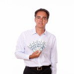 Hispanic man holding money while standing