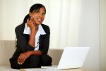 Pensive businesswoman with notes and laptop