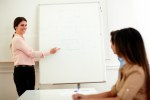 Professional caucasian lady pointing at whiteboard