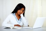 Reflective young woman studying on laptop