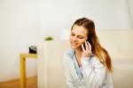 Relaxed woman using a mobile phone at home