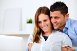 Romantic young couple at home looking to laptop