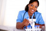 Smiling black nurse working with a test tube