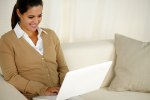 Smiling latin young female using her laptop