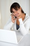 Smiling woman looking at you in front of laptop