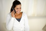 Smiling young woman conversing on cellphone