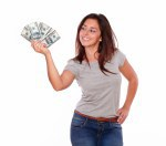 Smiling young woman holding cash dollars