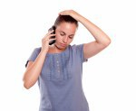Stressed young woman conversing on cellphone