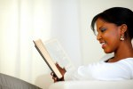 Stylish young relaxed woman reading a book