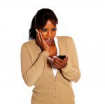 Surprised black woman reading message on cellphone