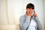 Surprised young woman conversing on phone
