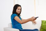 Woman using a television remote