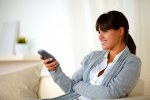 Young female sitting on couch with remote