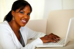 Young woman looking at you while working on laptop