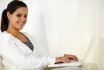 Young woman looking at you working on laptop