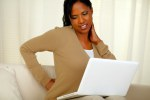 Young woman with back pain working on laptop
