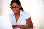 Young woman with black glasses working on laptop
