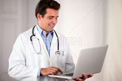Adult hispanic doctor using his laptop