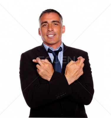 Adult latin man crossing arms and fingers