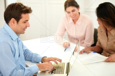 Adult male employee working with his laptop