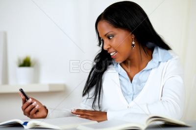 African student reading a message on cellphone